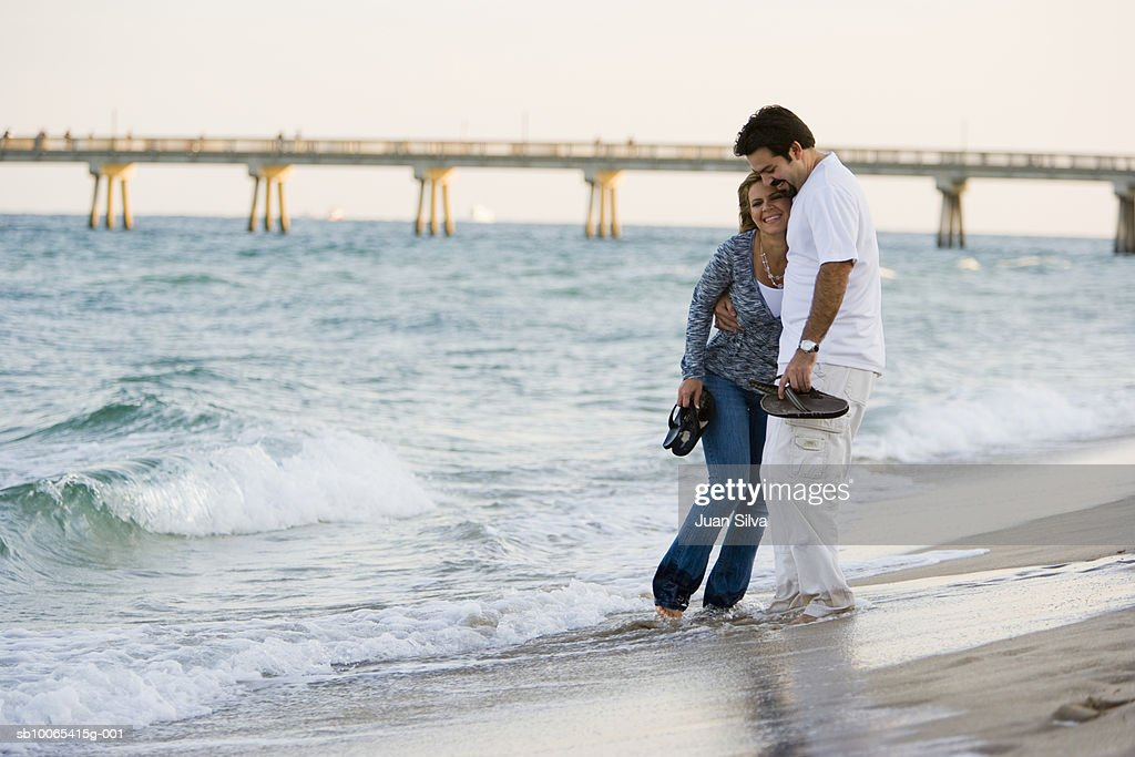 Couple embracing with shoes off on beach : Foto stock
