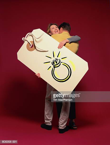 Couple embracing, woman holding tag showing engagement ring (Composite