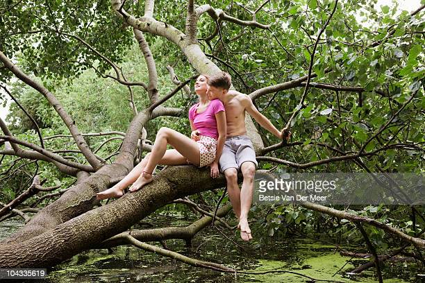 couple embracing,sitting on tree trunk.
