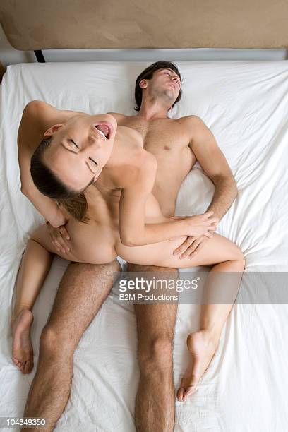 couple engaged in sexual intercourse on bed - chica desnuda fotografías e imágenes de stock