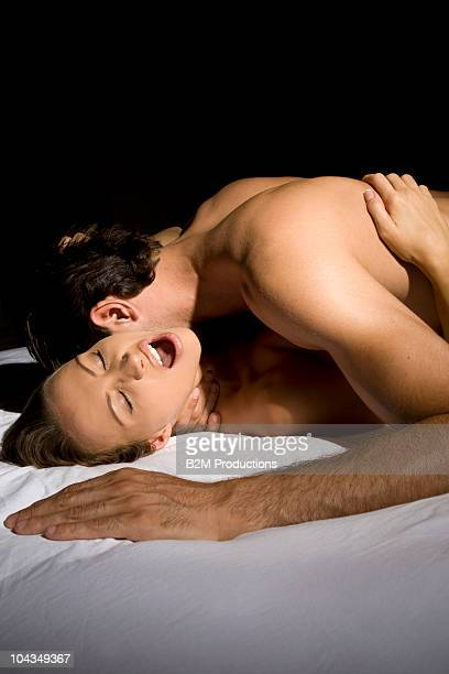 Couple engaged in sexual intercourse on bed