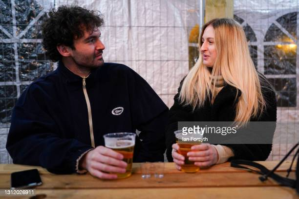 Couple enjoy a drink at the Switch bar in Newcastle shortly after midnight following the easing of lockdown measures on April 12, 2021 in Newcastle...
