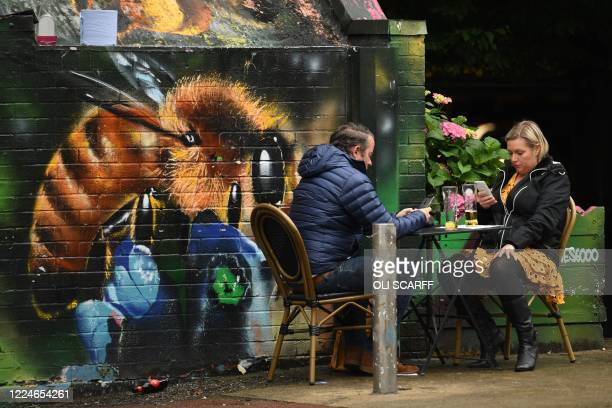 Couple enjoy a drink sitting at an outside table of a bar in Manchester, north-west England, on July 4 as restrictions are further eased during the...