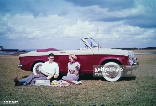 Couple enjoy a picnic in front of their two tone Singer Gazelle I 2 door convertible coupe car in England in September 1956.