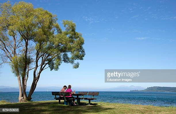 Couple enjoy a picnic on shore of a lake
