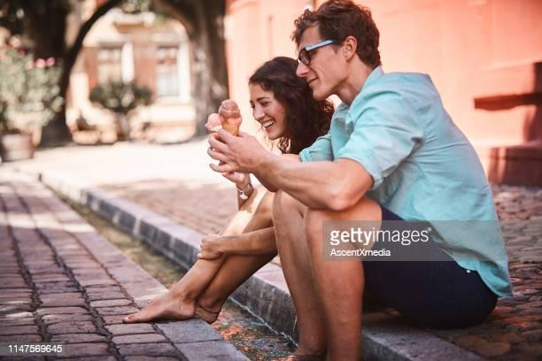 couple enjoy cultural food on a city promenade - gelato italiano foto e immagini stock