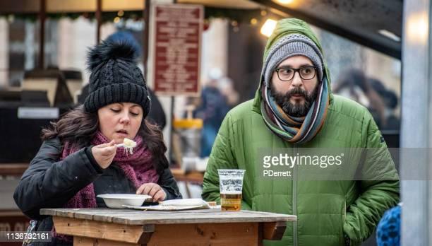 カップルはプラハのクリスマスマーケットで食べ物や飲み物をお楽しみください。