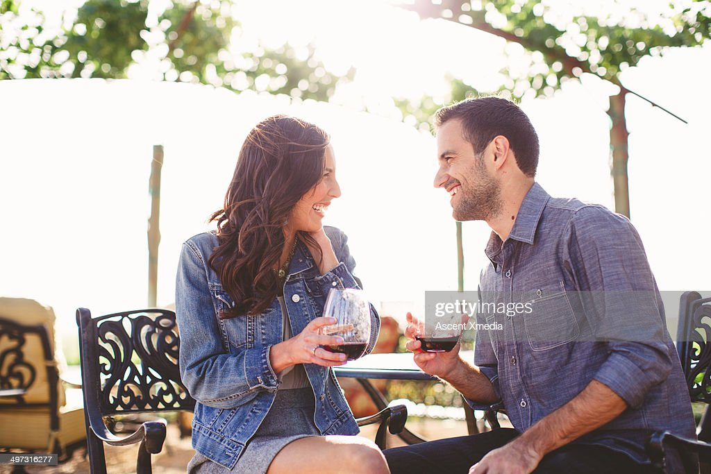 Couple enjoy glasses of wine at outdoor bar : Stock Photo