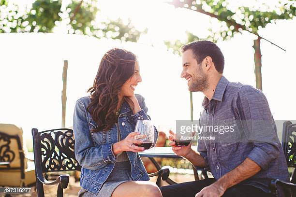 Couple enjoy glasses of wine at outdoor bar