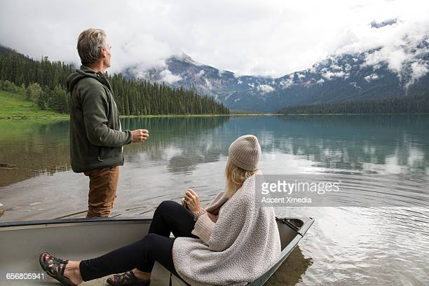 Couple enjoy hot drink from canoe, mtn lake
