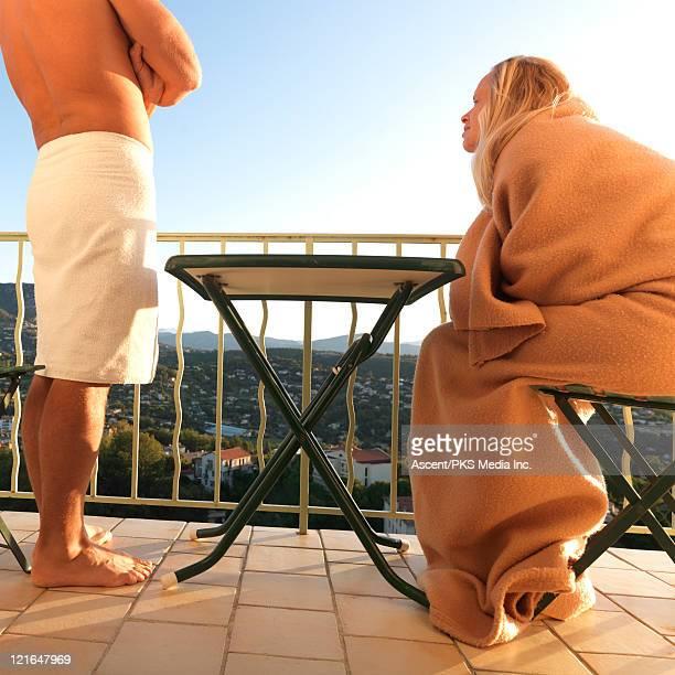 Couple enjoy sunrise on terrace, above town