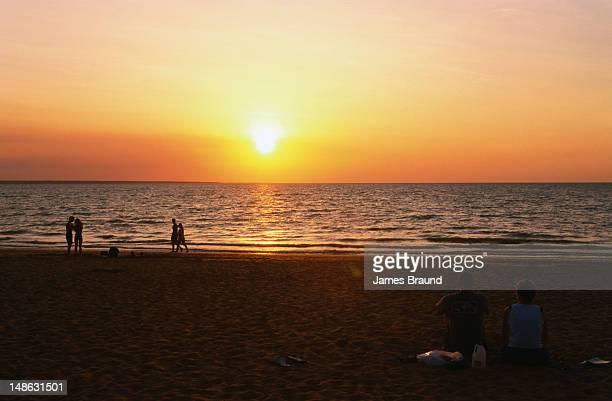 Couple enjoy sunset picnic at Mindil Beach market.