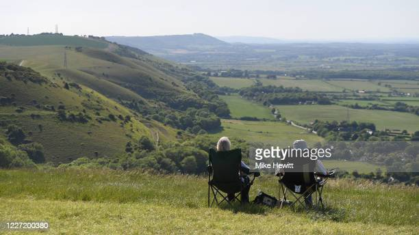 Couple enjoy the view from the National Trust beauty spot Devil's Dyke on May 26, 2020 in Brighton, United Kingdom. The British government continues...