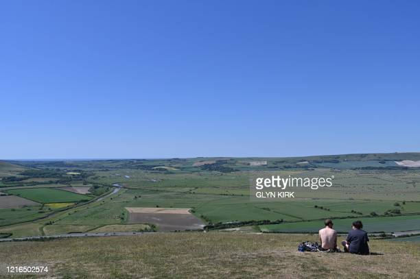 Couple enjoy the view from the top of Mount Caburn, a prominent high point on the South Downs east of Lewes in southern England on May 31, 2020 on...