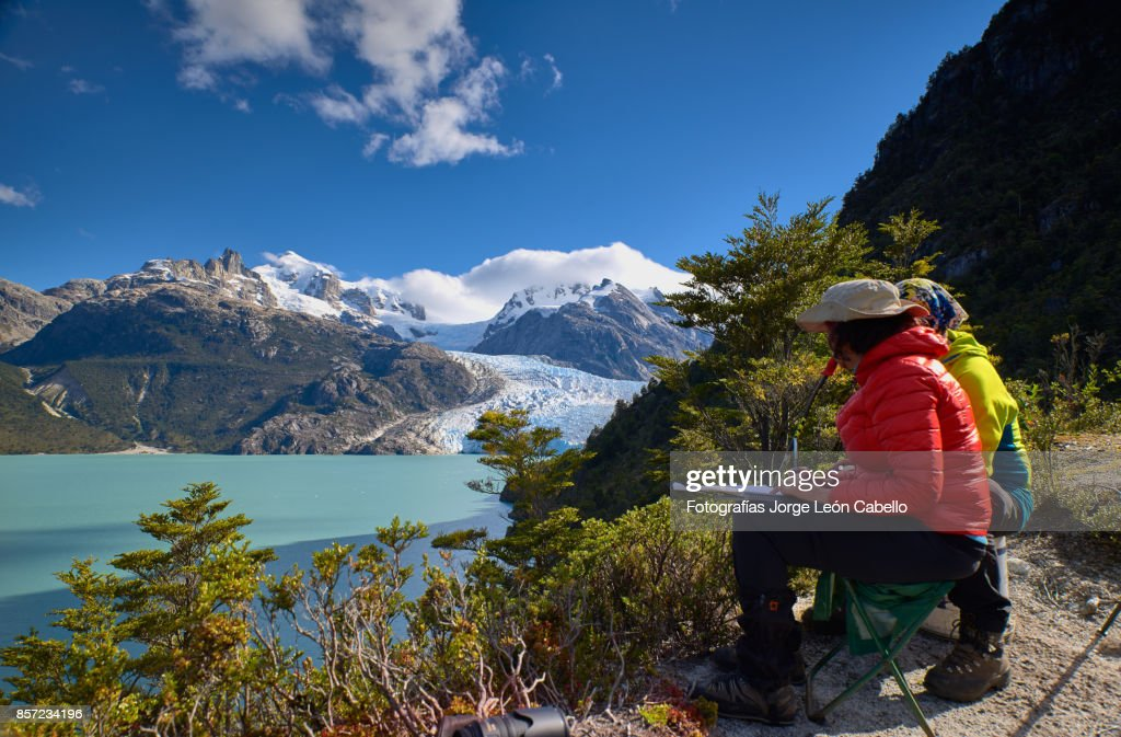 A couple enjoy the view of lake Los Leones and the glacier : Stock Photo