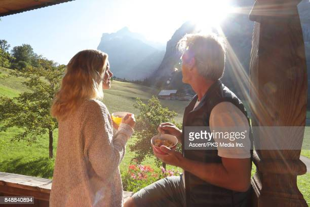 Couple enjoy view from mountain chalet veranda