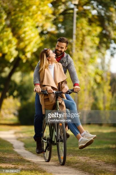 paar genieten van een fietstocht in het park - jong koppel stockfoto's en -beelden