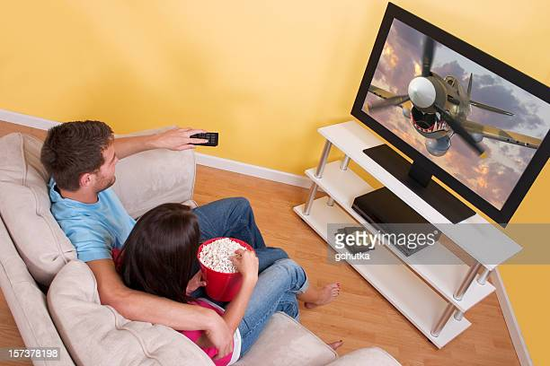 a couple enjoying a cartoon on tv with popcorn - lcd television stock pictures, royalty-free photos & images
