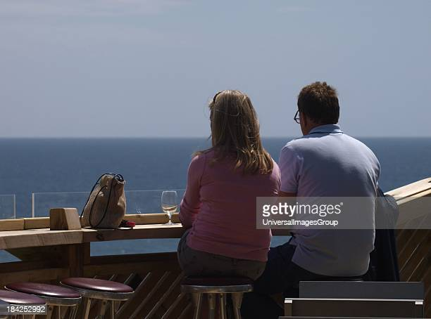 Couple enjoying a drink at a bar overlooking the sea Devon UK