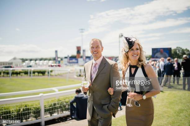 couple enjoying a drink on race day - horse racing stock pictures, royalty-free photos & images