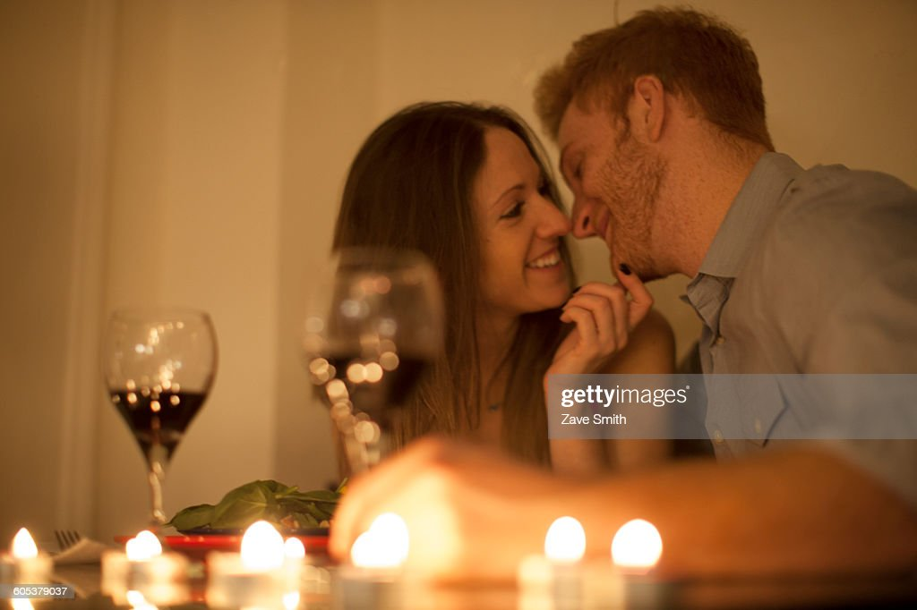 Couple enjoying a glass of red wine by candlelight, face to face smiling : Stock Photo
