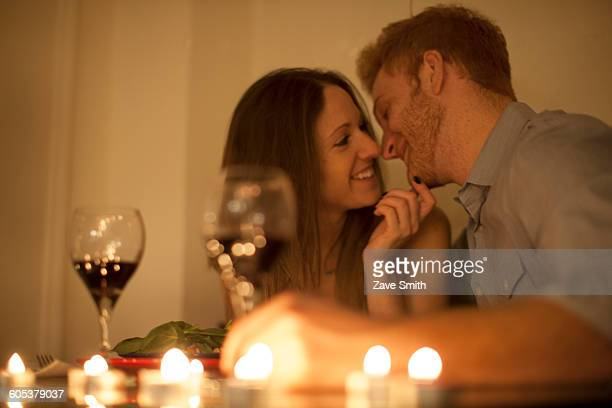 Couple enjoying a glass of red wine by candlelight, face to face smiling