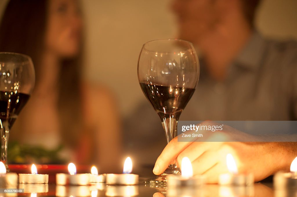 Couple enjoying a glass of red wine by candlelight : Stock Photo