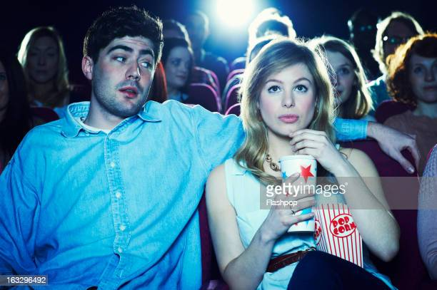couple enjoying a movie at the cinema - dating stock-fotos und bilder