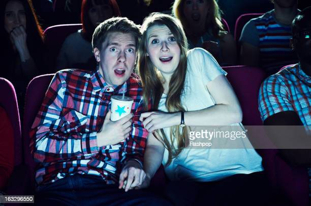 couple enjoying a movie at the cinema - terrified stock pictures, royalty-free photos & images