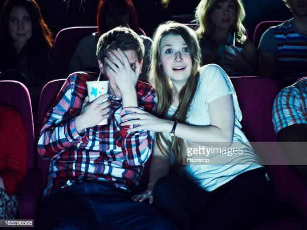 couple enjoying a movie at the cinema - filmindustrie stock-fotos und bilder