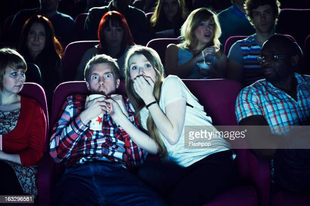 couple enjoying a movie at the cinema - scary movie stock photos and pictures