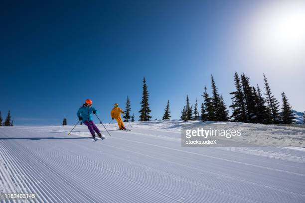 couple enjoying a ski vacation - alpine skiing stock pictures, royalty-free photos & images