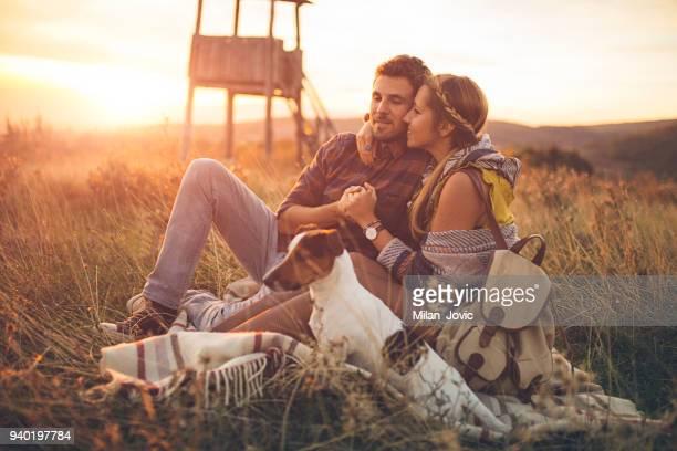 Couple enjoying a sunny day with dog