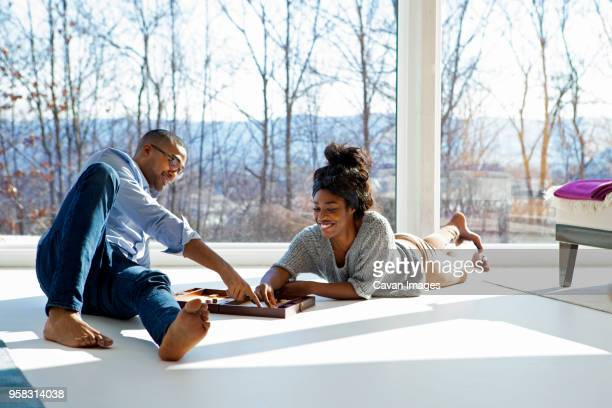 Couple enjoying backgammon game at home