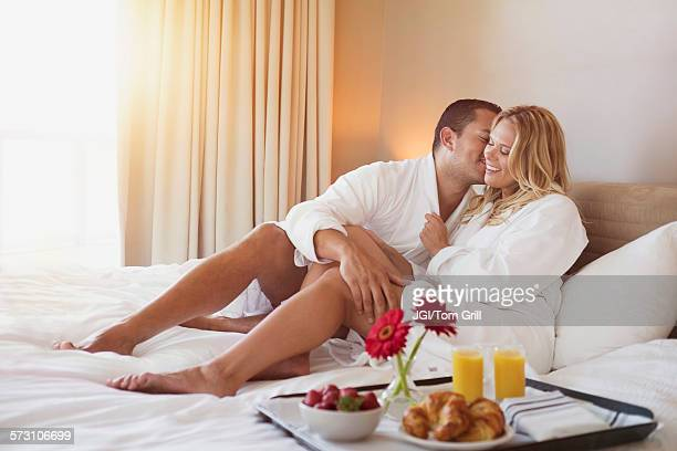 couple enjoying breakfast in bed in hotel room - honeymoon stock photos and pictures