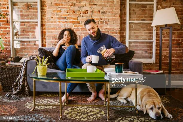 Couple enjoying breakfast on sofa in living room