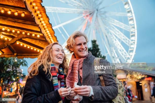 couple enjoying christmas fair - hyde park london stock photos and pictures