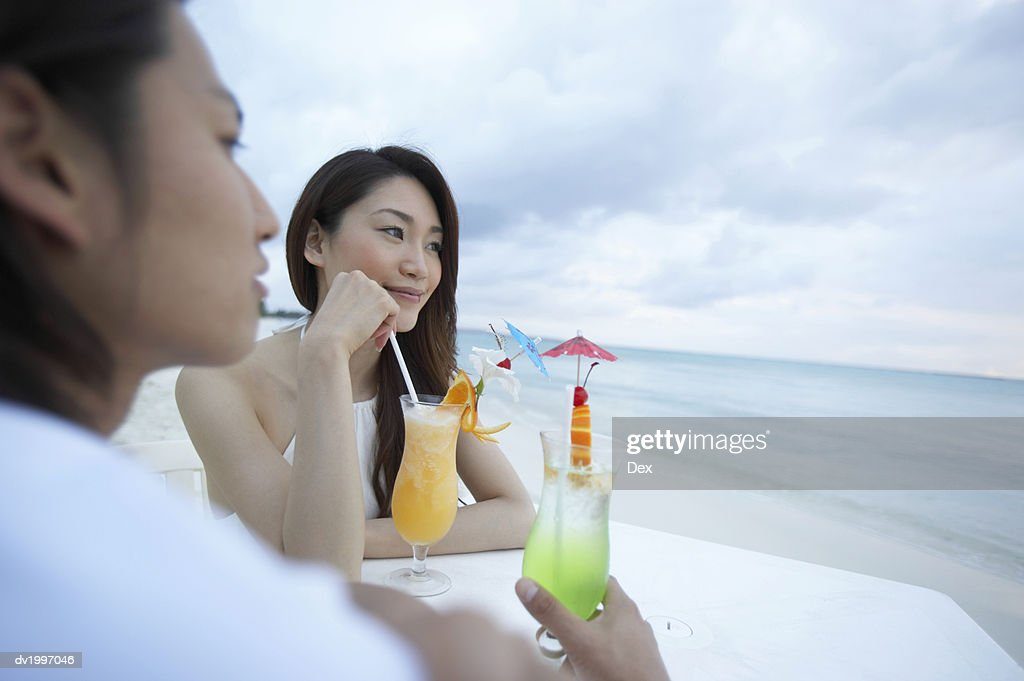 Couple Enjoying Cocktails at a Table on a Beach : Stock Photo