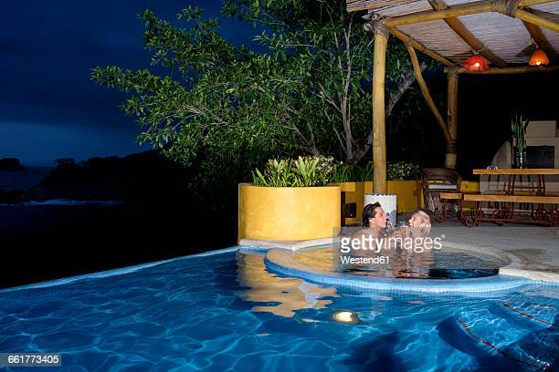 Couple enjoying cocktails in swimming pool at night