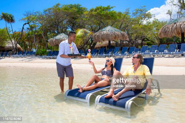 couple enjoying cocktails on vacation - serving food and drinks stock pictures, royalty-free photos & images
