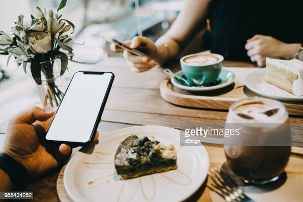 couple enjoying coffee and cake while using smartphone in cafe - couple chocolate stock pictures, royalty-free photos & images