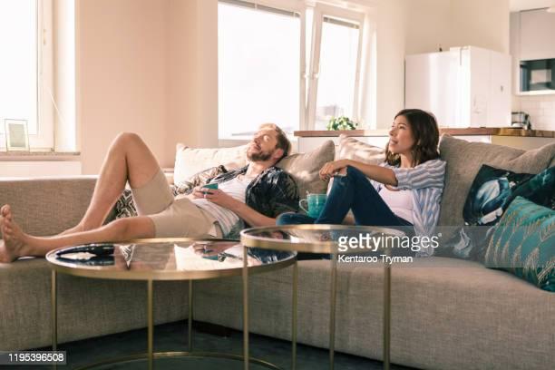 couple enjoying coffee while resting on sofa in apartment - relationship stockfoto's en -beelden