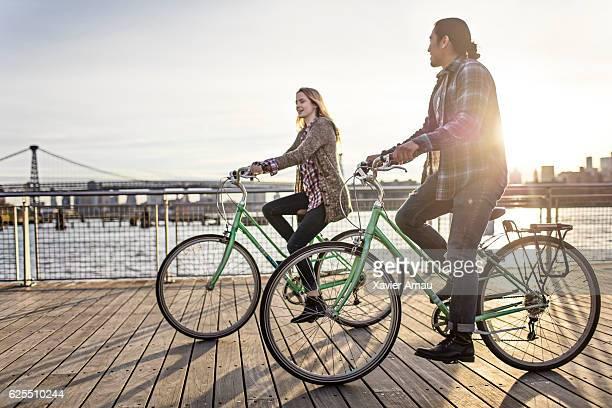 couple enjoying cycling on promenade - ウォーターフロント ストックフォトと画像