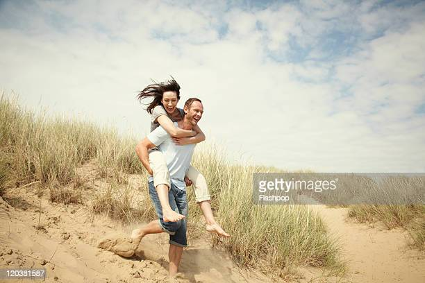 couple enjoying day out at the beach - mid adult couple stock pictures, royalty-free photos & images