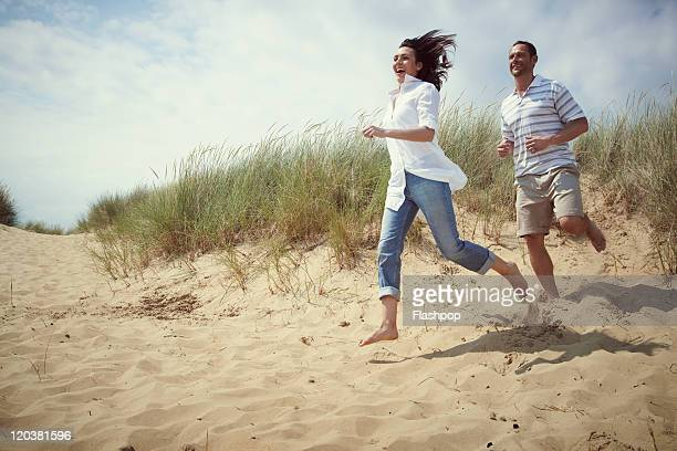 couple enjoying day out at the beach - sand stock pictures, royalty-free photos & images