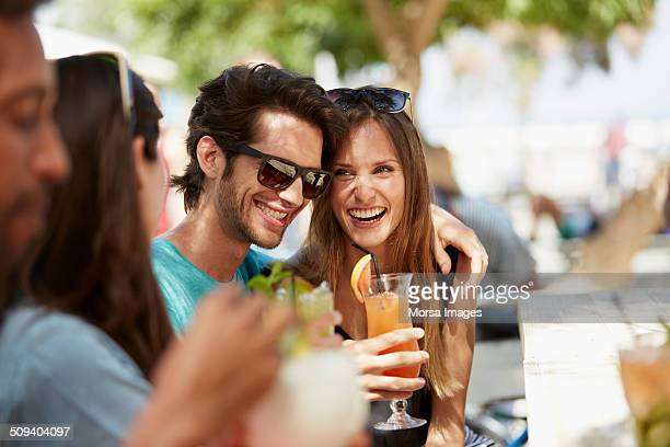 Couple enjoying drinks with friends at restaurant