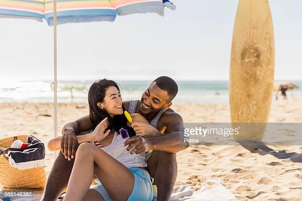 Couple enjoying flavoured ice cream at beach