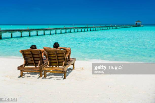 couple enjoying holidays at dhiffushi holiday island, maldives - idyllic stock pictures, royalty-free photos & images