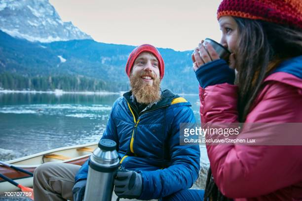 Couple enjoying hot drink by Eibsee Lake at base of Zugspitze, Garmisch-Partenkirchen, Bavaria, Germany