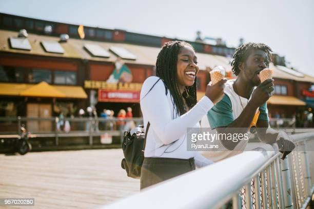couple enjoying ice cream on seattle pier - seattle foto e immagini stock